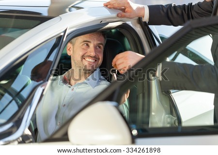 Picture of showroom client sitting in his new car - stock photo