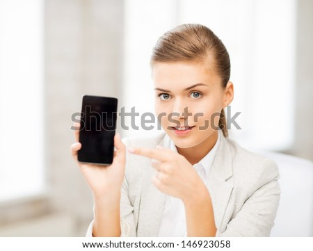 picture of smiling businesswoman with smartphone in office - stock photo