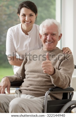 Picture of smiling old man sitting on wheelchair and carer - stock photo
