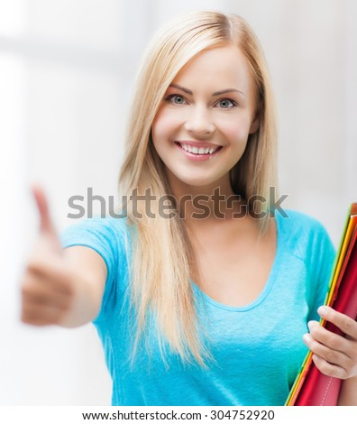 picture of smiling student with folders showing thumbs up - stock photo