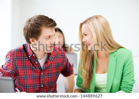 picture of smiling students looking at each other at school