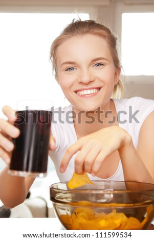 picture of smiling teenage girl with chips and coke - stock photo