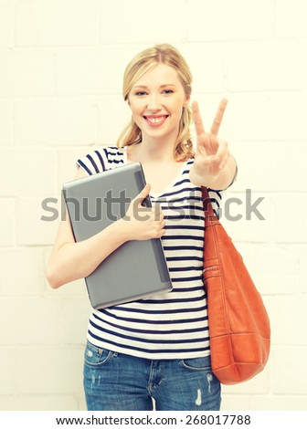 picture of smiling teenage girl with laptop showing victory sign - stock photo