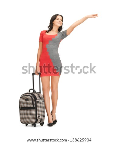 picture of smiling woman in dress with suitcase hitchhiking - stock photo
