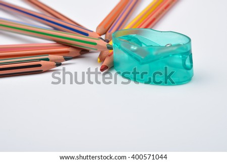 Picture of some pencils with stripes of different colors and pencil sharpener on a white background. Selective focus - stock photo