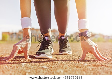 Picture of sports woman standing in start position, preparing to run. - stock photo