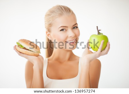 picture of sporty woman with apple and hamburger