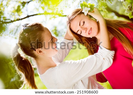 Picture of spring sun flare effects and two young pretty ladies having fun standing enjoying under blooming tree  - stock photo