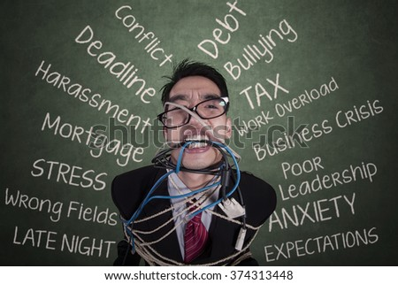 Picture of stressed young businessman tied with a rope on the chair in the classroom - stock photo