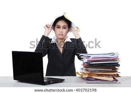 Picture of stressful businesswoman put a paperwork on her head with a laptop and a pile of document on the table - stock photo