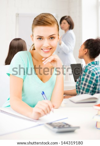 picture of student girl with notebook and calculator at school - stock photo