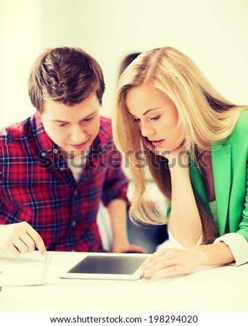 picture of students looking at tablet pc at school