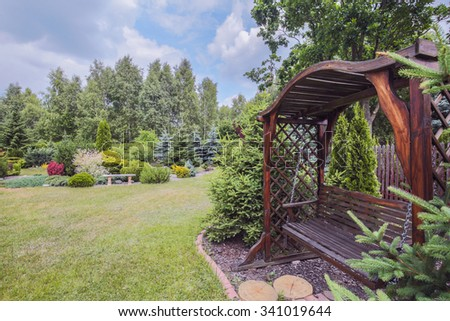 Picture of stylish wooden garden bench with pergola - stock photo