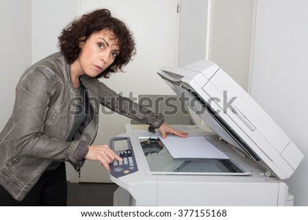 Picture of surprised businesswoman with smoking copier