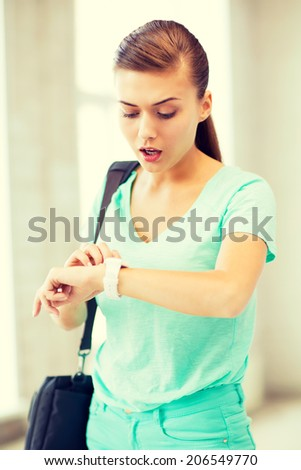 picture of surprised student girl looking at clock - stock photo