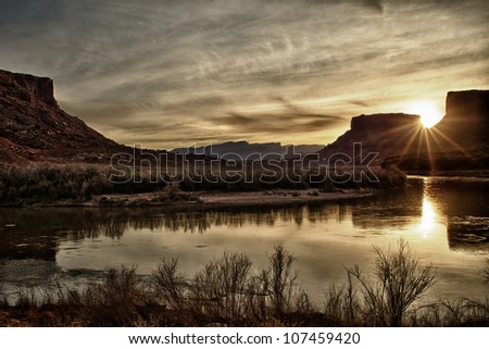 Picture of the sun setting behind Utah canyons and the Colorado river. Taken in Utah. - stock photo