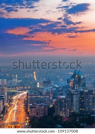 Picture of the sunset lighting of the city of Almaty, made from the top of the mountain. - stock photo