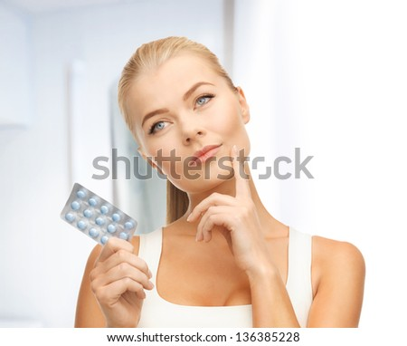 picture of thoughtful young woman with pills - stock photo