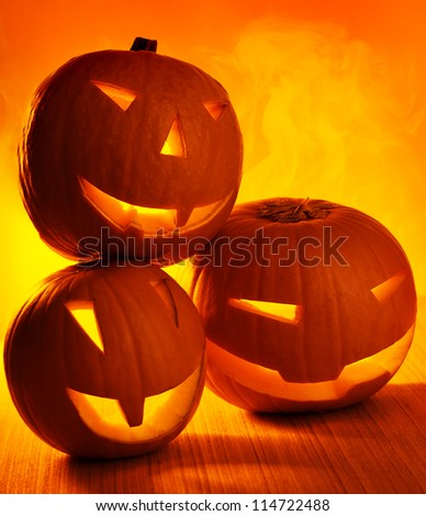Picture of three pumpkins border, Halloween party, october holiday, carved pumpkin candle, jack-o-lantern, Halloween decoration, happy gourd face with glowing shine on wooden table - stock photo