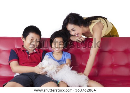 Picture of two cheerful children sitting on the sofa with their mother while playing a maltese dog - stock photo