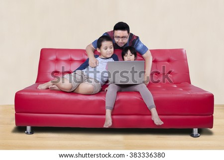 Picture of two cute children sitting on the sofa while using laptop computer with their father at home - stock photo