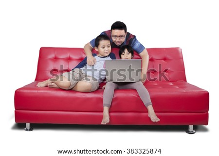 Picture of two cute children using laptop together with their father on the sofa while browsing internet online - stock photo