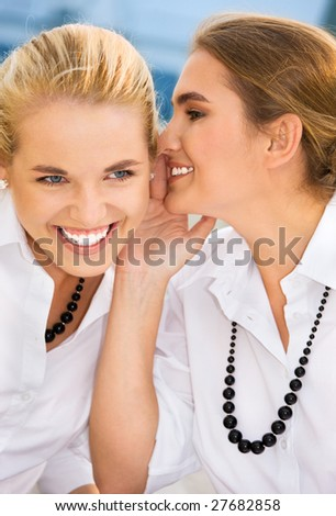 picture of two happy young girlfriends sharing secrets - stock photo