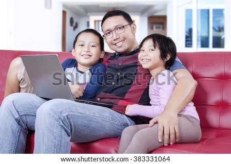 Picture of two lovely children and their father smiling at the camera while sitting on the sofa with laptop computer - stock photo