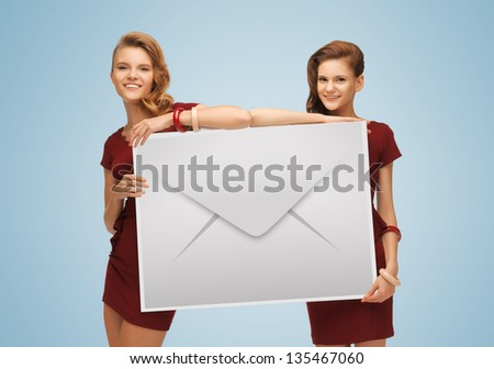 picture of two lovely girls holding big envelope - stock photo