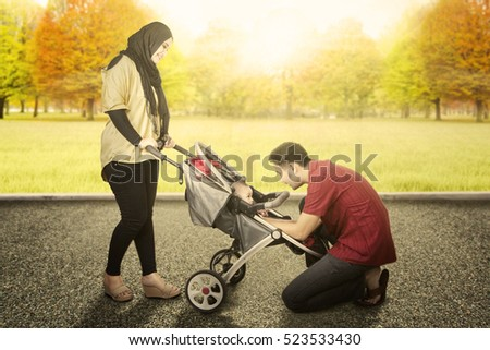 Picture of two Muslim parents carrying their son in the stroller while playing together in park autumn