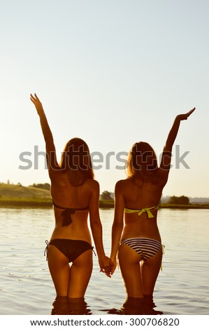 Picture of two sexy best girlfriends in bikini having fun together holding hands up to sky on summer sunset outdoors copy space background - stock photo