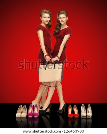picture of two teenage girls in red dresses with bag - stock photo