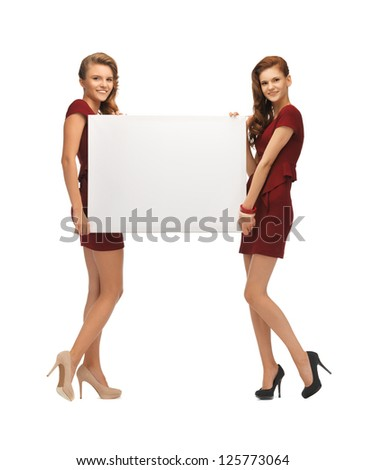 picture of two teenage girls in red dresses with blank board - stock photo