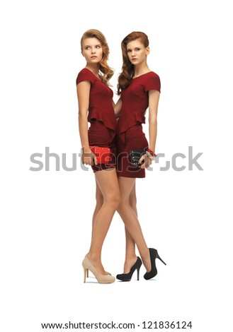 picture of two teenage girls in red dresses with clutches - stock photo