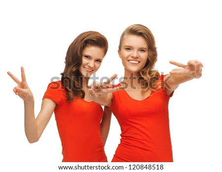 picture of two teenage girls in red t-shirts showing victory sign - stock photo