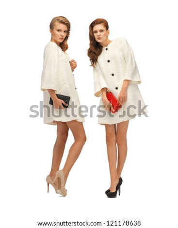 picture of two teenage girls in white coats with clutches - stock photo