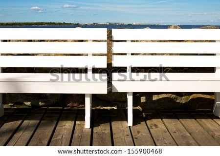 Picture of two white benches at a marina. Sea in the background - stock photo
