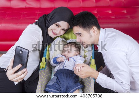 Picture of two young parents with their baby in the stroller, taking selfie picture together at home - stock photo