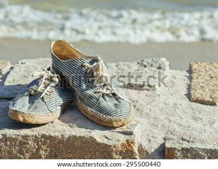 picture of vintage old shabby sneakers at seacost, real forgotten shoes close up - stock photo