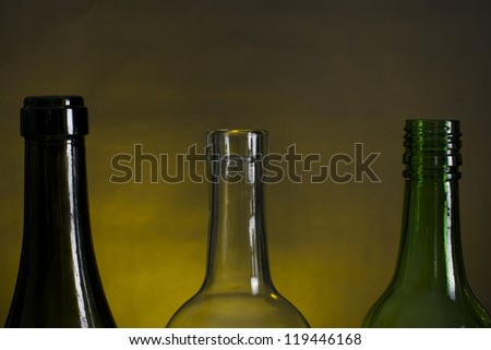 Picture of wine bottle necks on a row, on a yellow and black background - stock photo