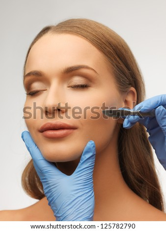 picture of woman face and beautician hands with scalpel - stock photo
