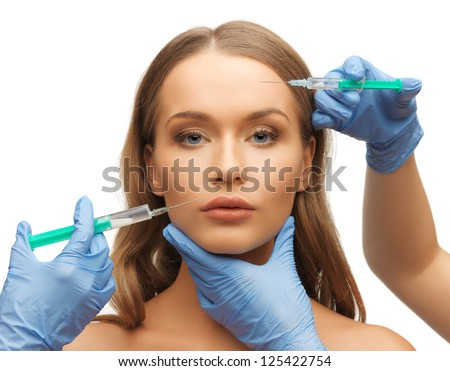 picture of woman face and beautician hands with syringes - stock photo