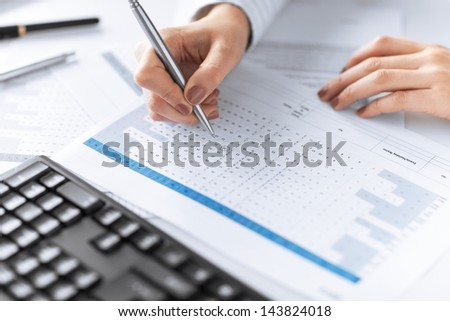 picture of woman hand writing on paper with numbers - stock photo