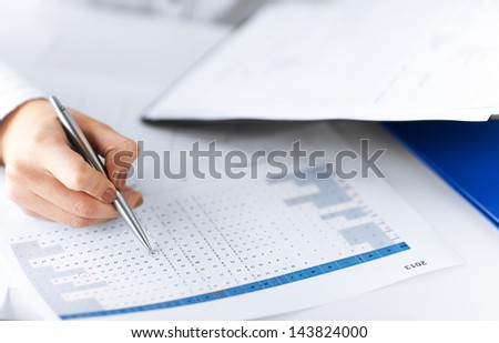 picture of woman hand wrtiting on paper with numbers