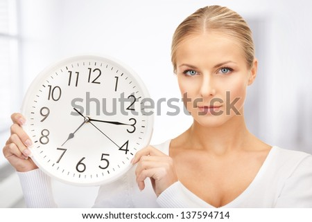 picture of woman holding big clock in office