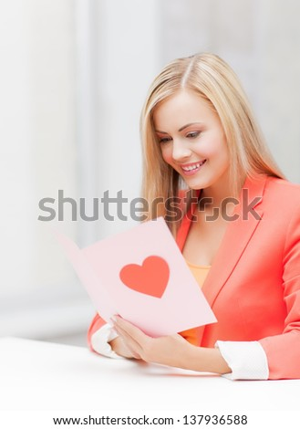 picture of woman holding postcard with heart shape. - stock photo
