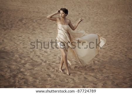 Picture of woman in flying gold cloth in the sand - stock photo
