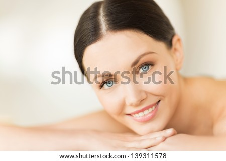 picture of woman in spa salon lying on the massage desk - stock photo