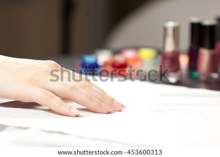 Picture of woman's hand and nail polishes at spa studio