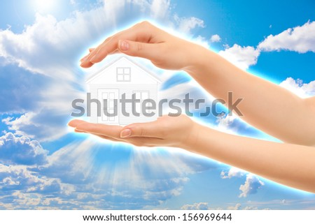 Picture of woman's hands holding a house isolated on white - stock photo